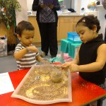 two children explore textures and volume - filling jars with oats